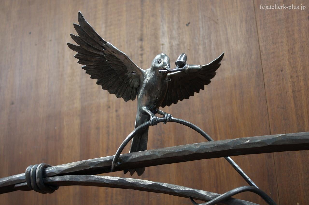 どんぐりをくわえたロートアイアンの小鳥
